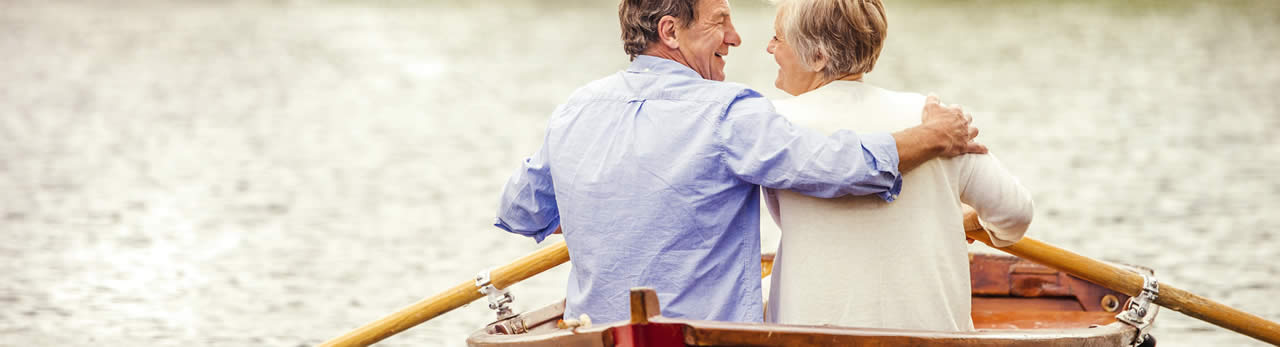 Couple hugging happily in a small rowing-boat on a lake