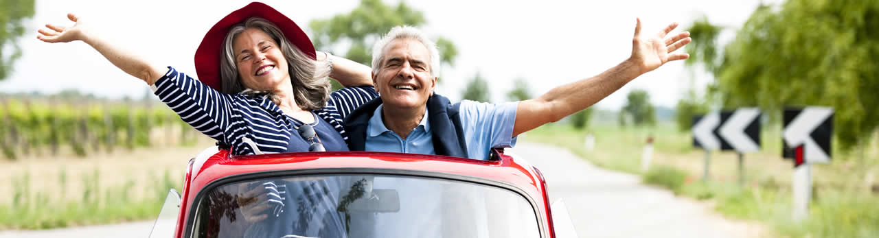 Couple with arms raised happily, standing up through car sunroof