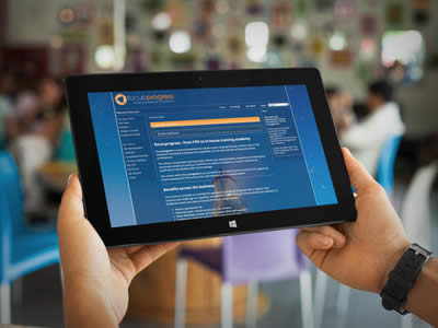 A man's hands holding a Microsoft tablet computer showing the focus:progress manager view - home page