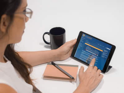 A young woman checking her personal student dashboard on the focus:progress manager page using an iPad